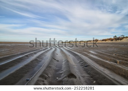 Sandy sea bottom during low tide and stripe of sea water - stock photo