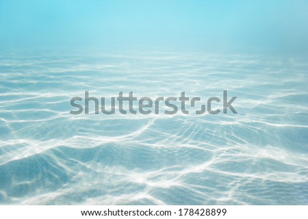 Sandy sea bottom with blue water background - stock photo