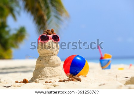 Sandy snowman and toys at tropical beach - stock photo