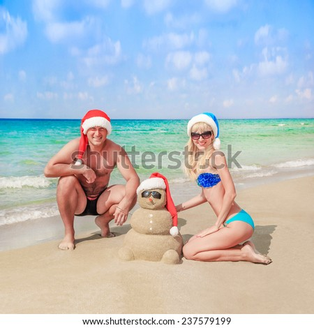 Sandy snowman in santa hat and young happy couple on sea beach. Holiday concept for New Year and Christmas Cards - stock photo