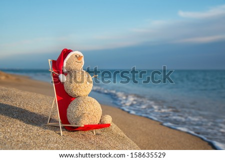 Sandy snowman in santa hat sunbathing in beach lounge. Holiday concept for New Years and Christmas Cards. - stock photo
