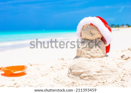 Sandy snowman with red Santa Hat on white Caribbean beach - stock photo