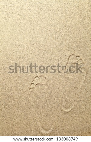 Sandy summer beach background with footprints. Copy space - stock photo