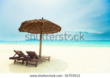 Sandy tropical beach with deck chairs in sunny day - stock photo