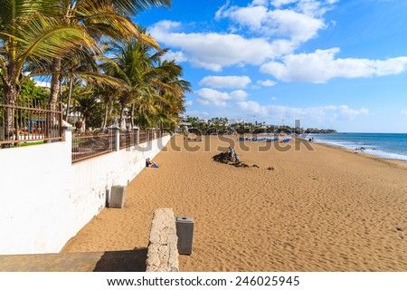 Sandy tropical beach with palm trees in Puerto del Carmen, Lanzarote, Canary Islands, Spain - stock photo