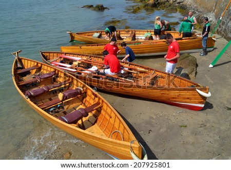 SANDYCOVE, IRELAND - JUNE 15: Unidentified competitors and beached wooden racing skiffs at The East Coast Rowing Council Races on June 15, 2014 in Sandycove, Ireland.  - stock photo