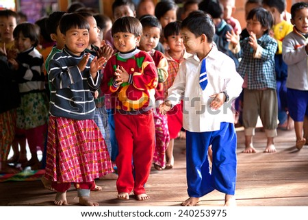 SANGKAR, SHAN STATE, MYANMAR - JANUARY 17: Young unidentified Burmese students dancing during their break time on January 17, 2011 in Sangkar village, Myanmar. - stock photo