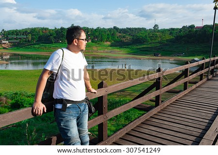 SANGKHLA BURI MAY 16 : People walk across the river on the old wooden bridge. Across the river in Sangkhlaburi Thailand on May 30, 2016.
