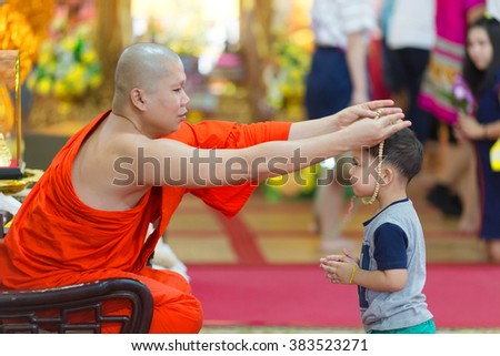 SANGKHLABURI, THAILAND, JANUARY 24, 2016 :  A buddhist monk is blessing a little boy  by inserting a rosary necklace around his neck in the Wat Wang Wiwekaram temple, Sanghklaburi, Thailand