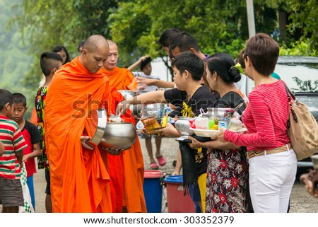Sangkla Buri , Kanchanaburi, THAILAND - OCT 26 : Buddhist monks are given food offering from people for End of Buddhist Lent Day. on October 26, 2013 in Sangkla Buri,Kanchanaburi,Thailand.