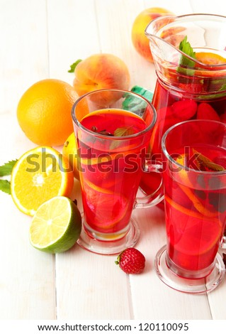 sangria in jar and glasses with fruits, on white wooden table - stock photo