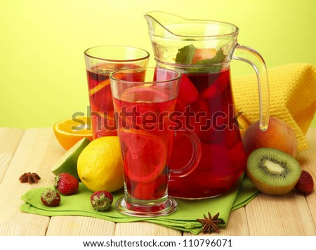 sangria in jar and glasses with fruits, on wooden table, on green background - stock photo