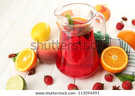 sangria in jar with fruits, on wooden table