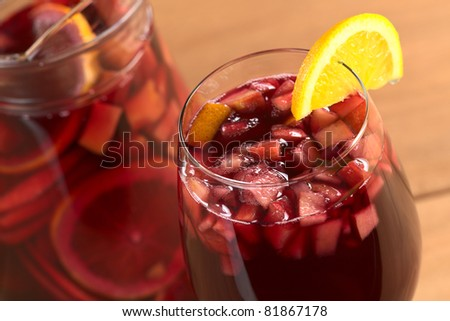 Sangria mixed with orange, apple, mango pieces served in wine glass garnished with orange slice on the rim (Selective Focus, Focus on the front of the orange slice garnish inside the glass) - stock photo