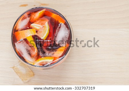 Sangria wine in the wineglass and pieces of ice on wooden table - stock photo