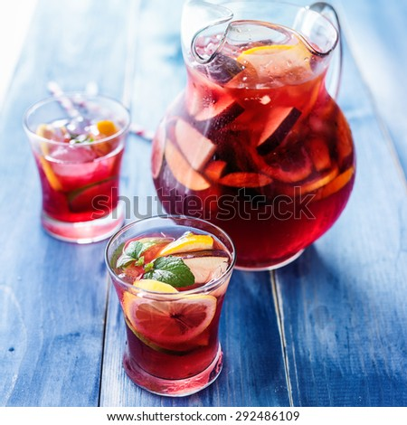 sangria with fruits and mint garnish in cups and pitcher in background - stock photo