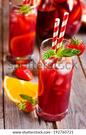 Sangria with strawberry, mint and orange in glasses and pitcher. Selective focus. - stock photo