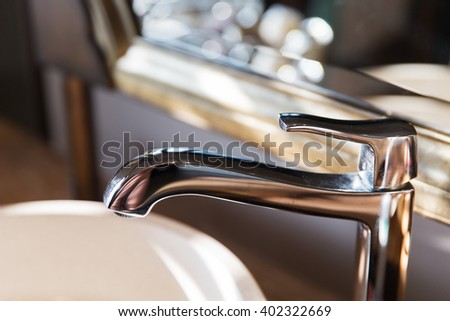 sanitary, plumbing and washing concept - close up of bath tap or faucet at bathroom - stock photo