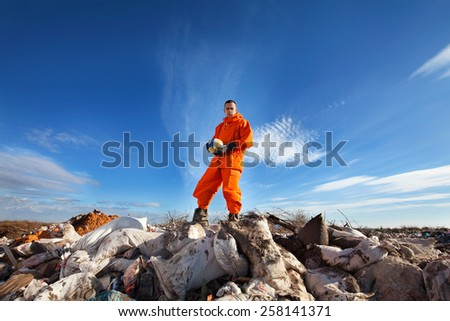 Sanitation worker standing among garbage bags holding a volleyball ball. - stock photo