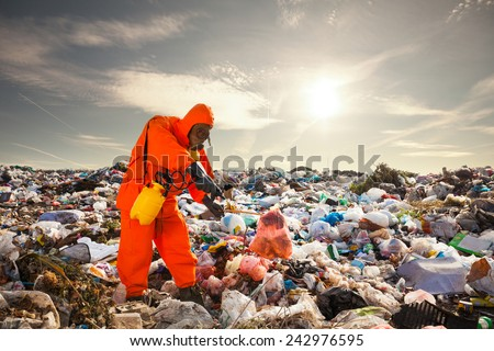 Sanitation worker working on the landfill - stock photo