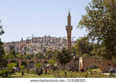 SANLIURFA, TURKEY - AUGUST 15: Unidentified visitors in a park with mosque. This clustered village attracts many visitors to its historical sights.  August 15, 2013 in Sanliurfa, Turkey.