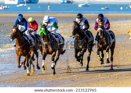 SANLUCAR DE BARRAMEDA, CADIZ, SPAIN - AUG 8: Unidentified riders race the first horses race called Gran Hipodromo Javier Pi���±ar on August 8, 2014 in Sanlucar de Barrameda, Cadiz, Spain. - stock photo