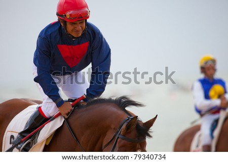 SANLUCAR DE BARRAMEDA, CADIZ, SPAIN - AUGUST 07: Unknown rider at the start of the horses races of the beach of Sanlucar de Barrameda on August 07, 2010 in Sanlucar de Barrameda, Cadiz, Spain. - stock photo
