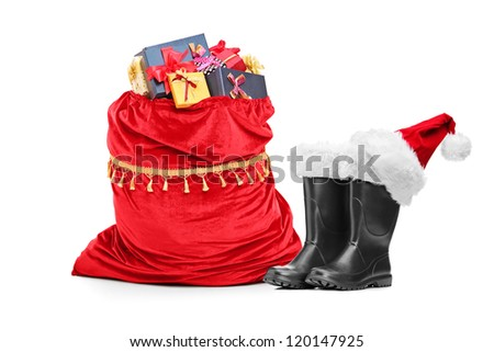 Santa accessories, pair of boots and bag full of presents isolated against white background - stock photo