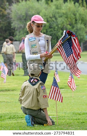 SANTA ANA, CA - MAY 25, 2013:  Boy Scouts and Girl Scouts of Orange County place flags next to the graves of veterans in preparation for Memorial Day services at Fairhaven Memorial Park and Mortuary. - stock photo