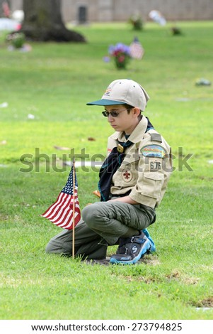 SANTA ANA, CA - MAY 25, 2013: Boy Scouts place flags at the grave sites of veterans in preparation for Memorial Day services. One scout pauses to pay his respects after placing a flag next to a grave. - stock photo