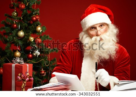 Santa answering Christmas letters by decorated fir-tree - stock photo