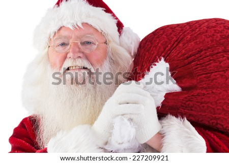 Santa carries his red bag an smiles on white background