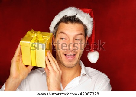 Santa  christmas guy in red with background holding and opening golden gift present