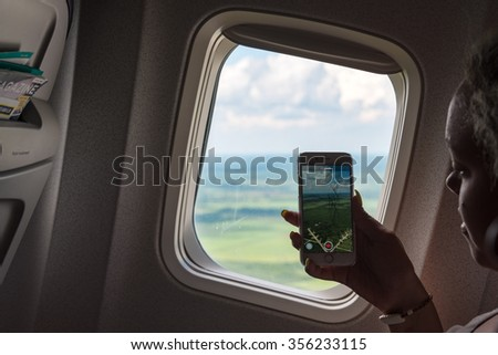 SANTA CLARA,CUBA-SEPTEMBER 27,2015: Tourist woman taking picture with cell from an airplane taking off in Cuba. Tourism has increased in the central part of Cuba due to the Santa Maria Key resorts - stock photo