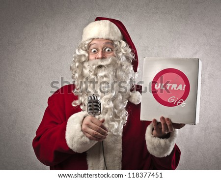 Santa Claus advertising a product on television - stock photo