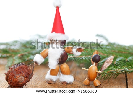 santa claus and angle tinkered with chestnuts and other on wooden board with copypsace - stock photo