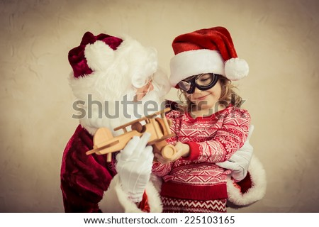 Santa Claus and child playing with vintage wooden plane at home. Christmas gift. Family holiday concept - stock photo