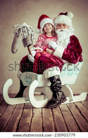 Santa Claus and child sitting on sleigh. Christmas gift. Family holiday concept - stock photo