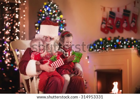 Santa Claus and children opening presents at fireplace. Kids and father in Santa costume and beard open Christmas gifts. Little girl helping with present sack. Family under Xmas tree at fire place. - stock photo