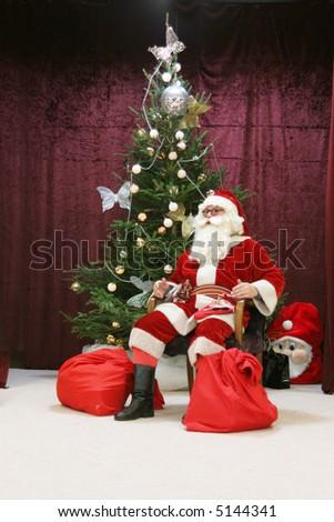 Santa claus and christmas tree - stock photo