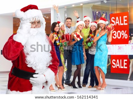 Santa Claus and group of happy people in shopping center.