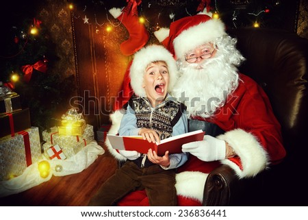 Santa Claus and happy boy sitting in Christmas room and reading a book. Christmas home decor.  - stock photo