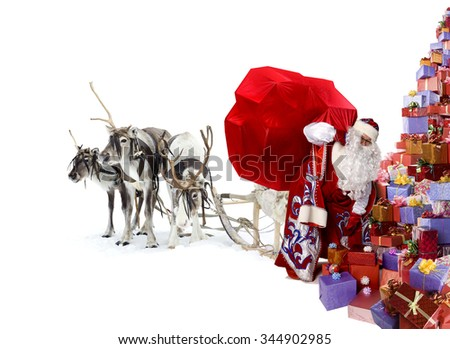Santa Claus and his deer have brought a lot of Cristmas gifts for you, isolated on white background. - stock photo