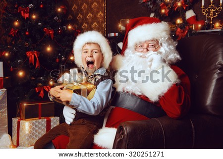Santa Claus and shouting cute boy sitting in Christmas room with gifts. Christmas home decoration.  - stock photo