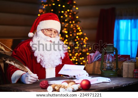 Santa Claus answering Christmas letters - stock photo