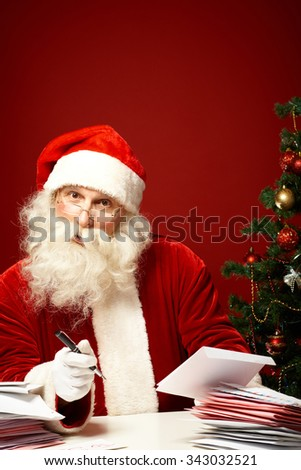 Santa Claus answering letters on Christmas eve - stock photo