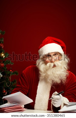 Santa Claus answering letters with Christmas wishes - stock photo