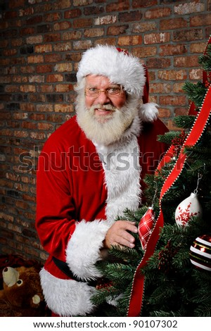 Santa Claus as he is sneaking around the Christmas Tree. - stock photo