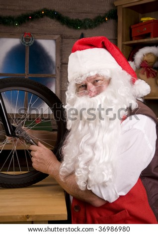 Santa Claus Assembling a Bicycle in His Workshop. Vertical Composition, closeup of Santa using wrench on Bike wheel.