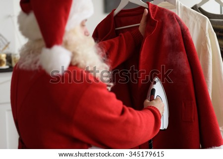 Santa Claus at Home Ironing his Costume - stock photo